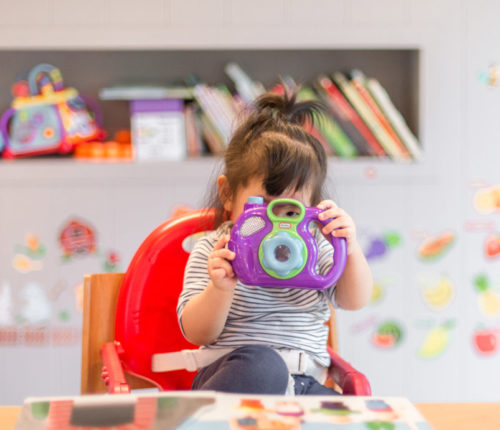 toddler girl in a high chair holding a toy camera